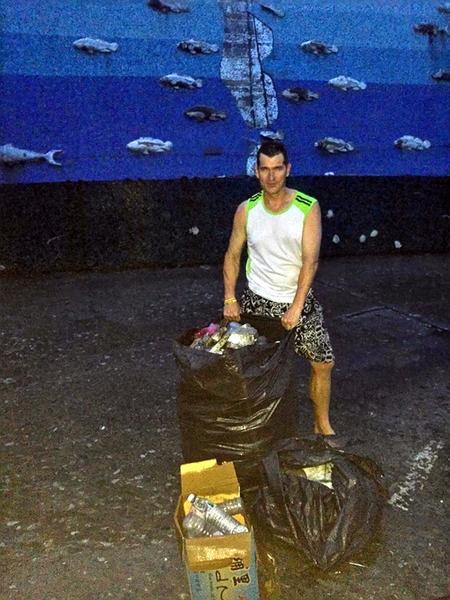 在台湾居住14年的美国人克里斯,20日傍晚驾驶艇到富冈港,看见港湾很脏,于是在海里捞垃圾,照片被钓客放在脸书,6000多人按赞。(胡姓钓客提供)