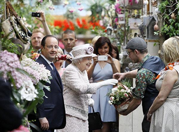 女王走訪花市時接受人們贈送給她的鮮花。(FRANCOIS MORI/AFP)