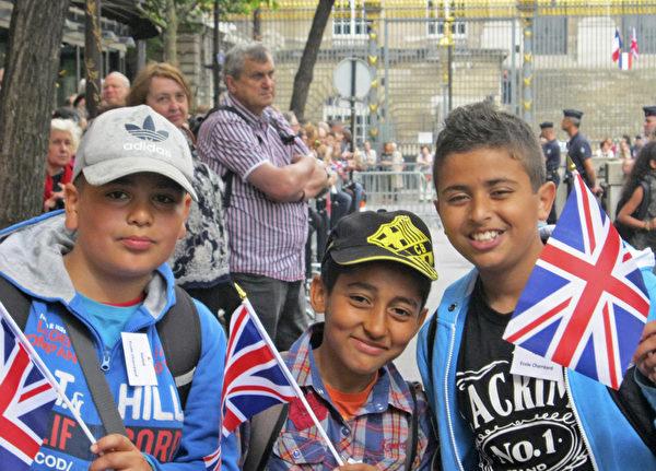 幾位法國少年手拿英國國旗,等待著女王的到來。(鄧蘊詞/大紀元)