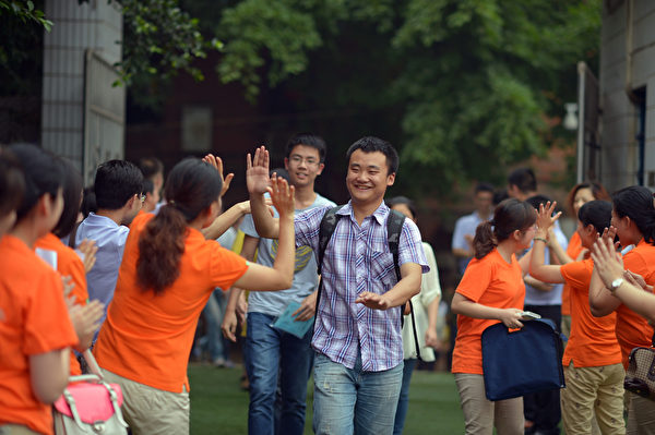 高考最后一天,统一着装的老师在考点外欢送考试结束的学生。(AFP)