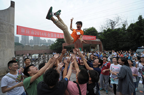 高考结束,重庆考生将老师抛到空中,以示庆祝。(AFP)