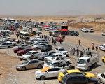 2014年6月11日,在伊拉克阿贝尔省库尔德民兵检查站前,等待过关的摩苏尔逃乱市民。(Emrah Yorulmaz/Anadolu Agency/Getty Images)