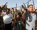 2014年6月16日,一名伊拉克儿童(中)与部落族人拿着他们的武器,展示他们愿意加入安全部队,与逊尼派叛军对抗,保卫巴格达。(AHMAD AL-RUBAYE/AFP/Getty Images)