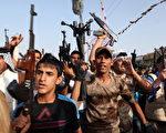 2014年6月18日,在伊拉克首都巴格达,什叶派男子拿着武器展示加入伊拉克安全部队,保卫首都的意愿。(ALI AL-SAADI/AFP/Getty Images)