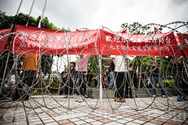中共國台辦主任張志軍26日在新北市五股區與新北市長朱立倫會面,歡迎群眾在警方布置的刀片蛇籠外聚集。(陳柏州/大紀元)