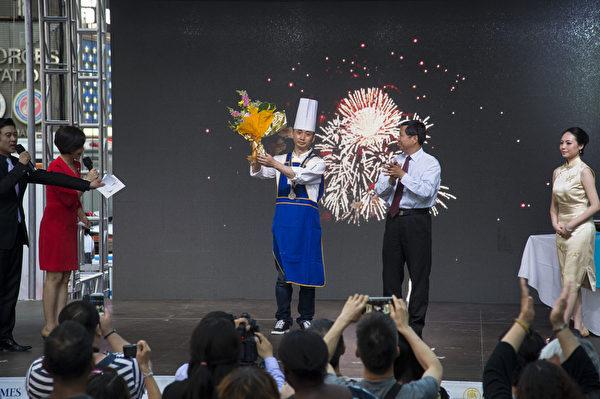 由新唐人电视台和大纪元时报联合举办的中国菜厨技大赛,6月26日在纽约时代广场圆满落幕。新唐人电视台董事长李琮亲自颁奖给得奖者,川菜 朱军(金奖)。 (戴兵/大纪元)