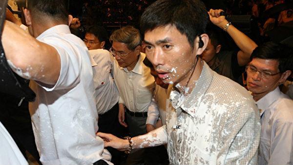 中共國台辦主任張志軍訪臺第三天晚上,遭到抗議人士潑白漆和灑冥紙抗議,他表情嚴肅心情顯然受到影響,在維安人員保護下快速進入會館。(AFP)