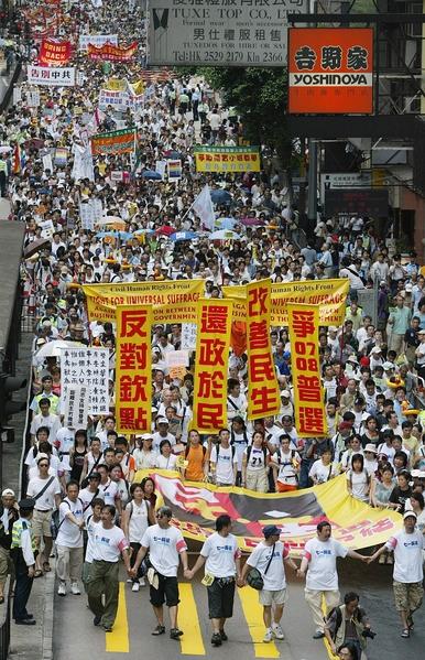 2005年七一大遊行的主題為「反對官商勾結,爭取全面普選」。圖為2005年7月1日,香港,參加遊行。(Richard A. BROOKS/AFP)
