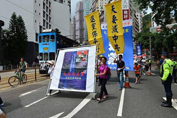 法轮功游行队伍整齐的幡旗横幅和天国乐团的雄壮演奏,成为七一游行中最瞩目的队伍。(Bill Cox/大纪元)