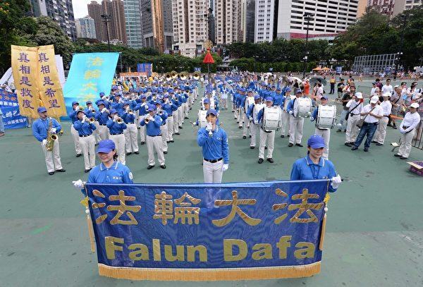 2014七一游行当天,法轮功学员组成的天国乐团在等候出发的同时,为在场参加游行的香港各界人士演奏。(宋祥龙/大纪元)