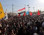 伊拉克什叶派大长老西斯塔尼呼吁圣战以对抗逊尼派叛军的进攻。图为2014年6月27日在首都巴格达响应号召、拿着武器的什叶派人群。(Stringer/Anadolu Agency/Getty Images)