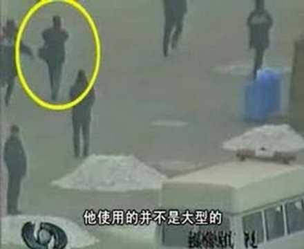 图中的男子在军警间从容拍摄,引起国际社会质疑。(央视自焚录影截图)