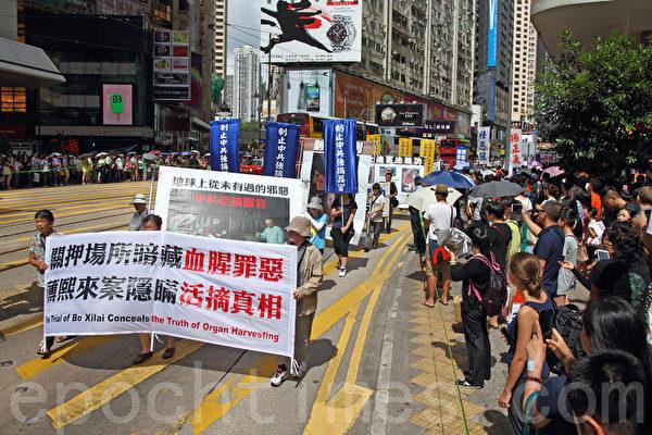 2014年7月19日,逾九百名法轮功学员在香港港岛区举行7.20十五周年反迫害集会游行,呼吁各界制止中共迫害法轮功。队伍从北角英皇道出发,途经多个闹市区抵达政府总部,吸引众多中港民众和游客驻足观看。(潘在殊/大纪元)