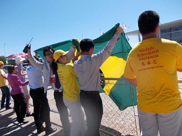 7月17日,法輪功學員們有秩序的於巴西總統府門前反對迫害,中共官員試圖蓋住抗議者卻毫無效果。(大紀元)