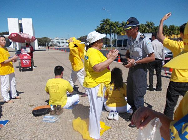 7月16日,法輪功學員們與巴西利亞刑警隊長澄清迫害真相。(大紀元)