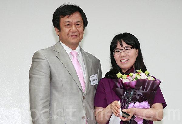 """7月22日,首尔""""外国劳工专门医院""""举办了建院10周年庆祝会,创建该院的慈善家金海性(左)为一名工作突出的护士颁奖。(全宇/大纪元)"""