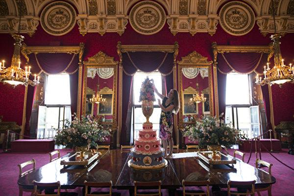 英皇家收藏基金會策展人安娜.雷諾茲在白金漢宮國宴廳裡佈置展品——1853年利奧波德王子的結婚蛋糕模型。(Oli Scarff/Getty Images)