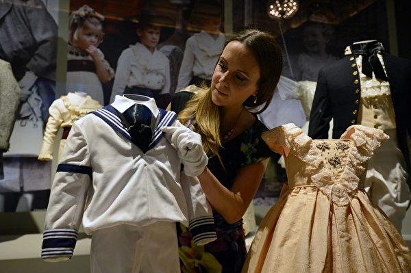 英皇家收藏基金會策展人安娜.雷諾茲在佈置展品——威廉王子在王室婚禮上穿過的水手服。(CARL COURT/AFP/Getty Images)