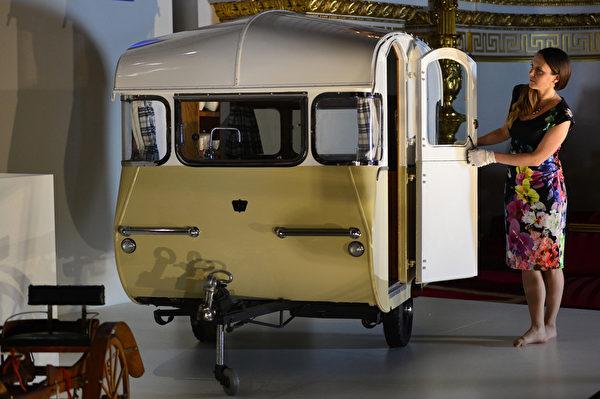 英皇家收藏基金會策展人安娜.雷諾茲介紹,查爾斯王子和弟弟們曾乘坐這輛玩具宿營車隨父親在王宮花園裡「旅行」。(AFP PHOTO / CARL COURT)