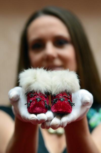 英皇家收藏基金會策展人安娜.雷諾茲手捧展品——英王愛德華七世孩童時穿過的鹿皮靴。(AFP PHOTO / CARL COURT)