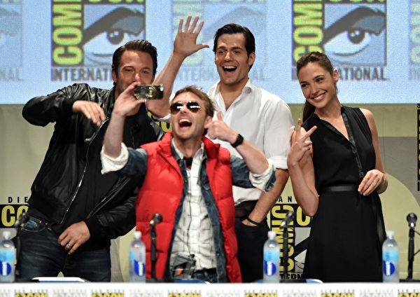 """主持人克里斯·哈德维克玩自拍,""""蝙蝠侠""""本·阿弗莱克、""""超人""""亨利·卡维尔与""""神奇女侠""""盖尔·加多全入镜。(Kevin Winter/Getty Images)"""