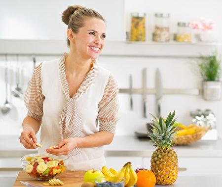 快樂的年輕主婦做水果沙拉。(fotolia)
