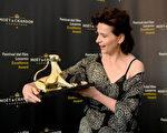 """朱丽叶‧比诺什(又译:茱丽叶‧毕诺许)不时端视她的""""金豹奖""""相当开心。(海鹏提供)"""