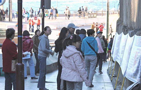 在澳大利亚悉尼歌剧院景点,中国大陆游客被法轮功真相横幅吸引。(明慧网)