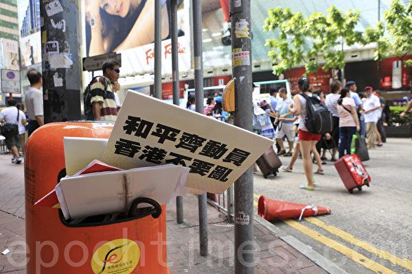 8.17中共重金花錢僱人遊行。不少遊行人士離開維多利亞公園後,就離去。圖為香港銅鑼灣街頭到處是被遊行人士隨意丟棄的反佔中紙牌等。(余鋼/大紀元)
