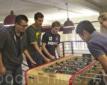 休息时间,Edison Ding(左)和同事玩桌上足球。(杨帆/大纪元)