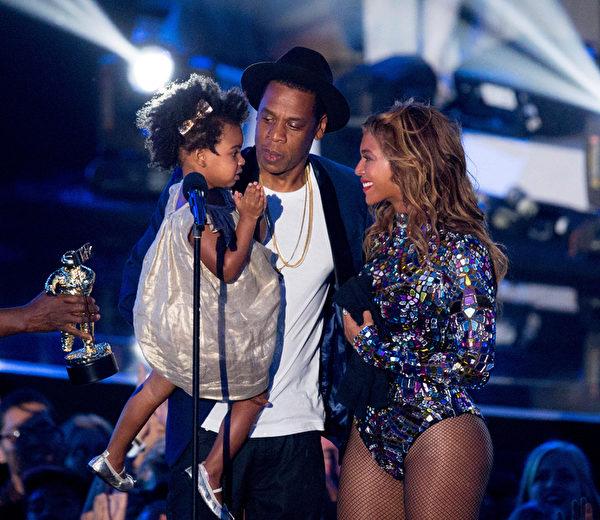 音乐人杰斯(中)怀抱女儿小艾薇,拥爱妻碧昂丝,领取最佳合作录影带奖。(Mark Davis/Getty Images)