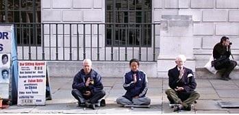 最早到倫敦中領館前靜坐抗暴的退休骨科醫生羅伯特.吉布森(Robert Gibson)(左一),右一為他的老友瑟羅爵士。(新紀元)