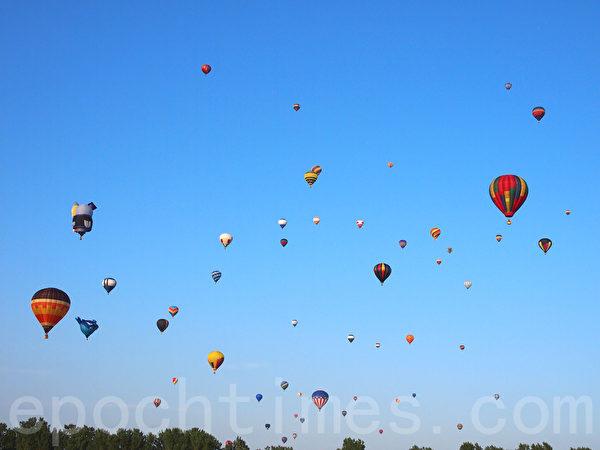 一顆顆色彩鮮豔的熱氣球相繼緩緩升起,天空彷彿變成綴滿了彩珠的幕布,璀璨壯觀。(譚雅/大紀元)