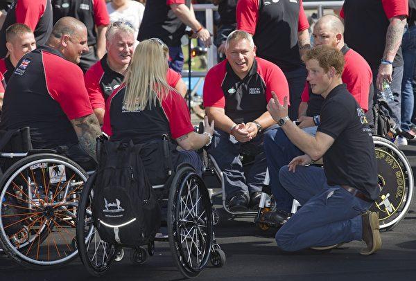 2014年8月13日,哈里王子(右跪地者)與準備參加不可征服運動會的英國傷殘軍人運動員們交談。(JUSTIN TALLIS/AFP/Getty Images)
