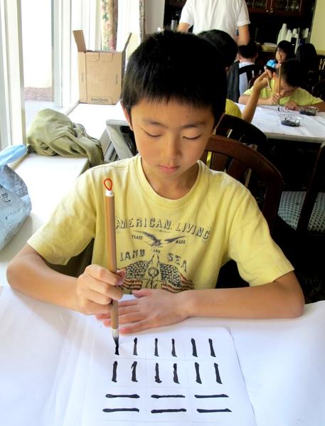 明慧学生练习写毛笔字。(明慧学校提供)