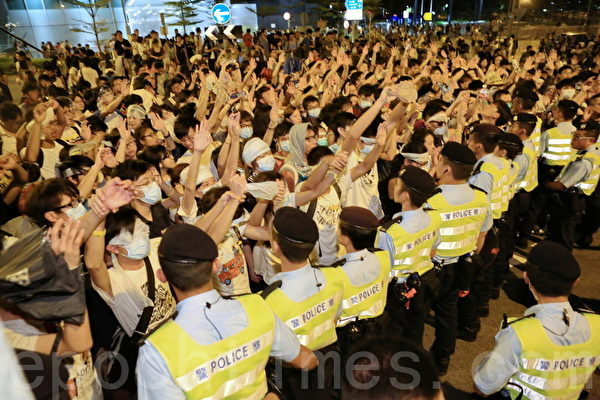 在政府總部前堅持罷課五天的學生,26日晚衝入佔領政府總部前的公民廣場。深夜,警方出動防暴警察和鐵馬架組成人牆,並使用胡椒噴霧對付學生。學生在現場高呼梁振英下台。(余綱/大紀元)