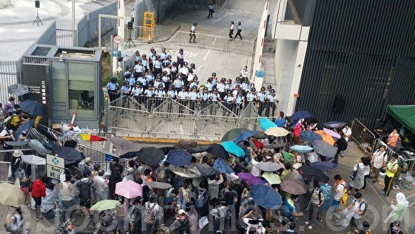 警方28日宣佈封鎖政府總部外集會現場一帶,添美道集會是非法集會;集會人士已張開雨傘,防備警方噴胡椒噴霧清場。(大紀元)