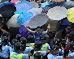 2014年9月28日,民眾以雨傘阻擋警方噴灑的胡椒與水柱。(aaron tam/AFP/Getty Images)