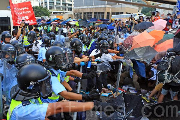 2014年9月28日,民眾以雨傘阻擋警方噴灑的胡椒與水柱。(余綱/大紀元)