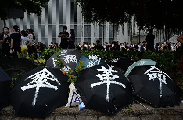 2014年9月29日,在港府總部前將兩傘打開罝地上。由於抗議者以兩傘抵擋警方的胡椒噴,外電報導稱這波民運為「雨傘革命」,港人則稱為「遮打革命」。(DALE DE LA REY/AFP)