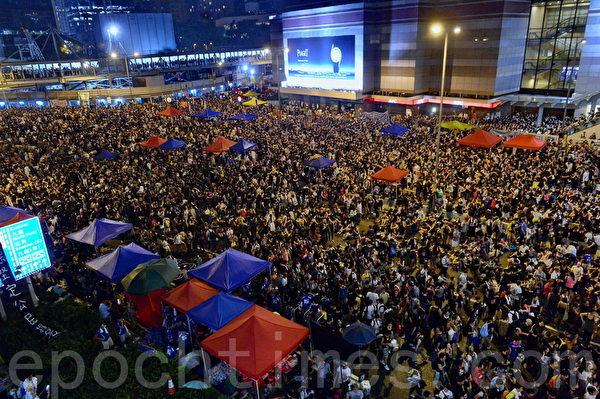 """香港""""雨伞行动""""进入第三天,继续有数以万计市民晚上在商业区金钟集会。尽管曾一度下起大雨,集会者仍然留守,坚持争取梁振英下台、人大道歉。(宋祥龙/大纪元)"""