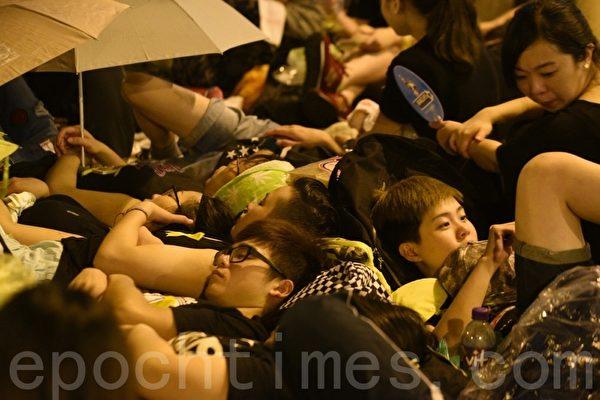 10月1日凌晨,香港金鐘的學運集會在雷雨交加下繼續進行。從天文台發出黃色暴雨警告到撤下,現場學生風餐露宿,一直堅守陣地,為的是兩個簡單訴求:特首梁振英下台、中共人大道歉。(文翰林/大紀元)