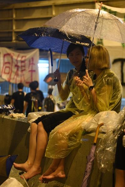 撐起雨傘,好朋友促膝談心。(大紀元資料圖片)