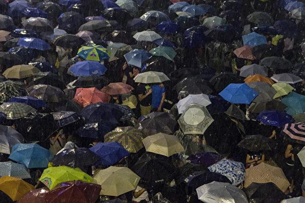 2014年9月30日,香港,晚間一度雷雨交加,但滂沱大雨沒有擊退群眾,現場一片傘海。(ANTHONY WALLACE/AFP)