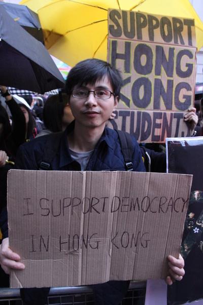 """大陆华人林先生在10月1日的集会中手举自制""""我支持香港的民主""""的纸板。(李景行/大纪元)"""