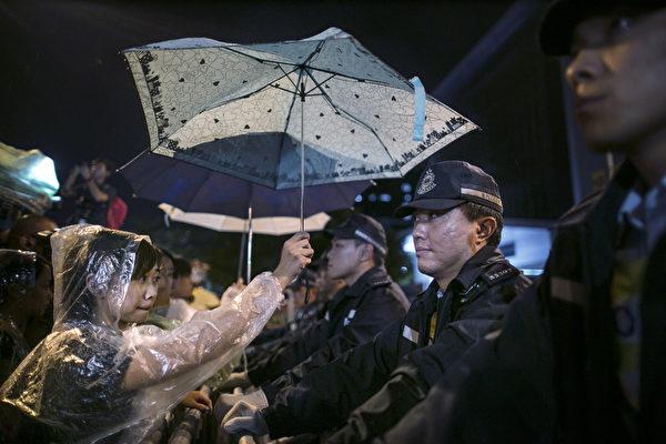在雨中,一位參與佔中活動的少女把傘舉到了虎視眈眈的警察的頭上,為他遮雨。(Paula Bronstein/Getty Images)