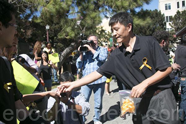 六四學運領袖、民運人士周鋒鎖在花園角為大家分發黃絲帶。(周鳳臨 /大紀元)