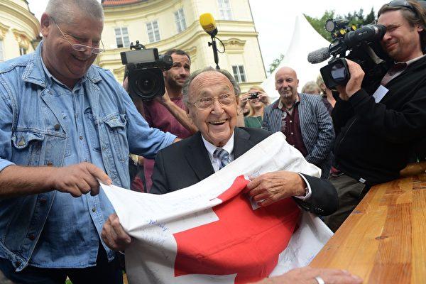 2014年9月30日,德国前外长汉斯-迪特里希‧根舍(中)在德国驻布拉格的使馆花园中与当年成功脱离东德的100多位难民以及很多协助他们的志愿者一起庆祝东德难民奔向西方自由世界25周年纪念日。(MICHAL CIZEK/AFP/Getty Images)