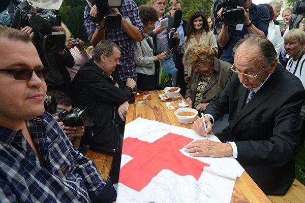 2014年9月30日,德国前外长汉斯-迪特里希‧根舍(右)在德国驻布拉格的使馆花园中与当年成功脱离东德的100多位难民以及很多协助他们的志愿者一起庆祝东德难民奔向西方自由世界25周年纪念日。(MICHAL CIZEK/AFP/Getty Images)