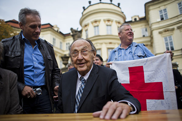 2014年9月30日,德国前外长汉斯-迪特里希‧根舍(中)在德国驻布拉格的使馆花园中与当年成功脱离东德的100多位难民以及很多协助他们的志愿者一起庆祝东德难民奔向西方自由世界25周年纪念日。(Matej Divizna/Getty Images)